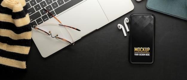 Bovenaanzicht van werktafel met mock up smartphone, oortelefoon, bril en laptop in kantoor aan huis