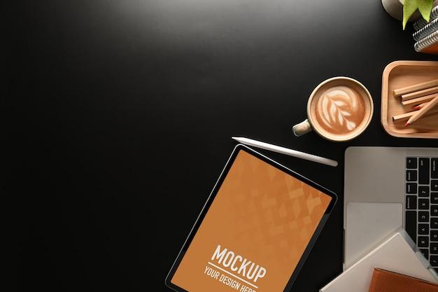 Bovenaanzicht van werktafel met mock-up tablet, laptop, briefpapier en kopie ruimte in kantoorruimte