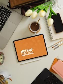 Bovenaanzicht van werktafel met tablet, laptop, smartphone, benodigdheden en decoraties