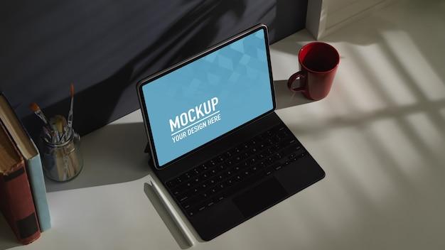 Bovenaanzicht van werktafel met tabletmodel, koffiemok en pen