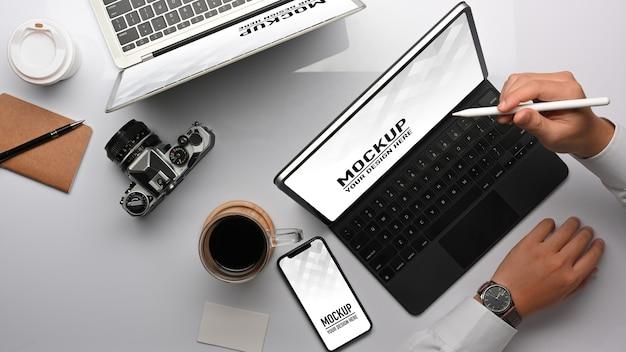 Bovenaanzicht van zakenman hand werken met tablet en smartphone mockup