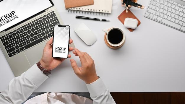 Bovenaanzicht van zakenmanhanden die smartphonemodel gebruiken