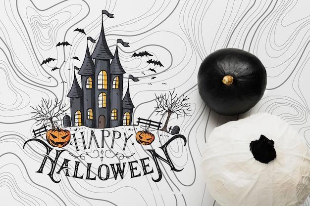 Bovenaanzicht van zwart-witte pompoenen met spookhuis