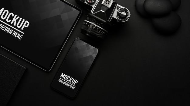 Bovenaanzicht van zwarte tafel met mockup voor smartphone en tablet