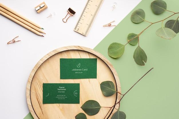 Bovenaanzicht visitekaartjes op hout met plant