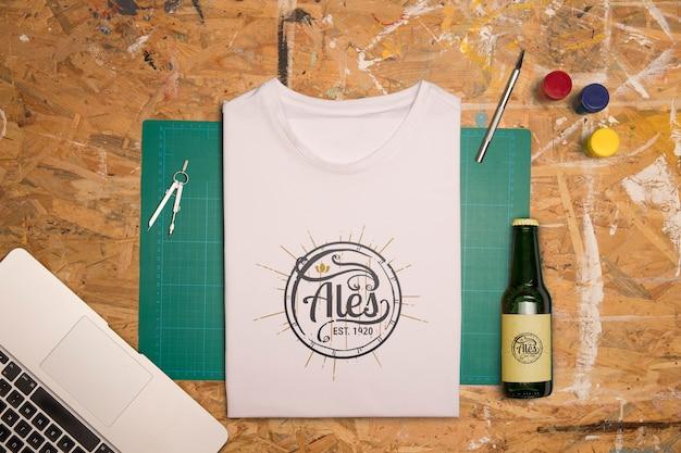 Bovenaanzicht wit gevouwen t-shirt en bier