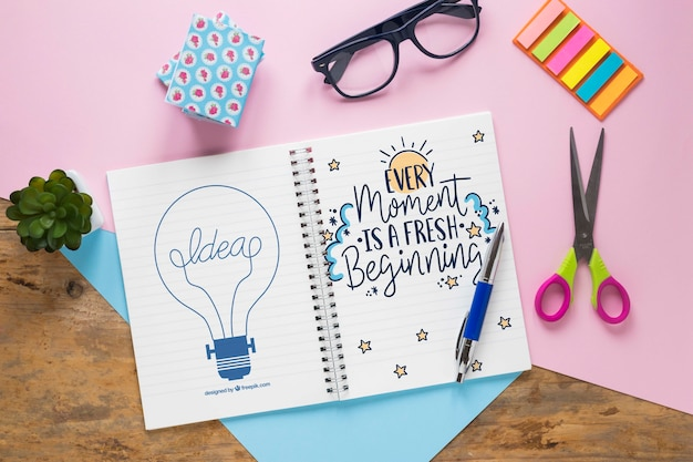 Brilenschaar en notitieboekje met motiverend bericht