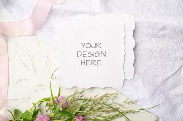Bruiloft mockup kaart met roze bloemen en delicate zijden linten op een witte ruimte