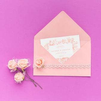 Bruiloft uitnodiging en bloemen op paarse achtergrond