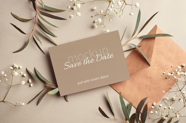 Bruiloft uitnodigingskaart mockup met envelop en eucalyptus en hypsophila twijgen