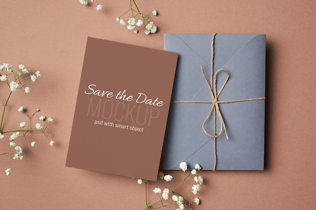 Bruiloft uitnodigingskaart mockup met envelop en witte hypsophila twijgen
