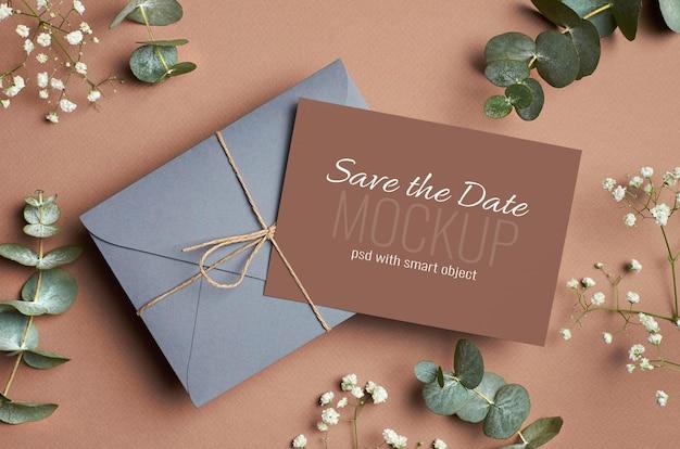 Bruiloft uitnodigingskaart mockup met envelop, eucalyptus en hypsophila twijgen