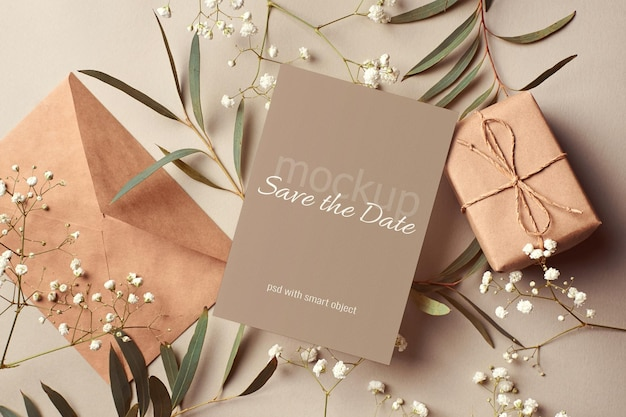 Bruiloft uitnodigingskaart mockup met envelop, geschenkdoos en eucalyptus en hypsophila twijgen