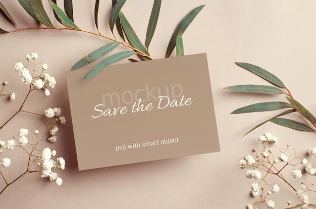 Bruiloft uitnodigingskaart mockup met eucalyptus en witte hypsophila twijgen