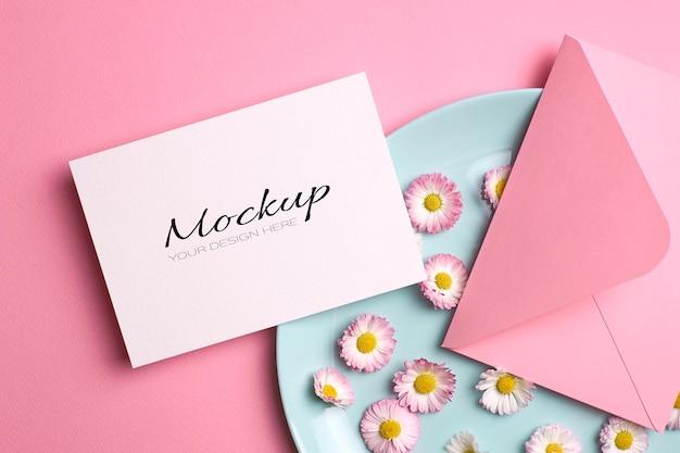 Bruiloft uitnodigingskaart mockup met roze envelop en madeliefjebloemen