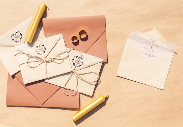 Bruine papieren enveloppen met bruiloft uitnodigingen en kaarsen