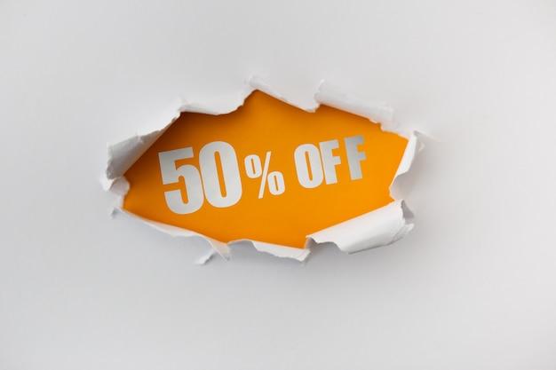 Buco strappato nel muro bianco di carta su uno sfondo giallo