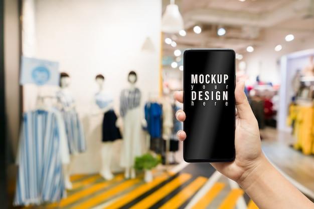 Burlarse del teléfono móvil de la tienda de moda de ropa femenina