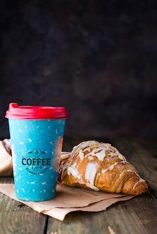 Café para llevar en una taza de papel con maqueta de croissants