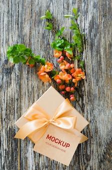 Caja de regalo con cinta de lazo, etiqueta en blanco y rama de floración delicada.
