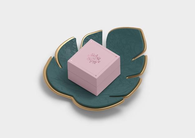 Caja de regalo de embalaje de joyas en una decoración de hojas de monstera