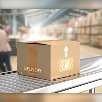 Caja sobre rodillo transportador en maqueta de almacén.