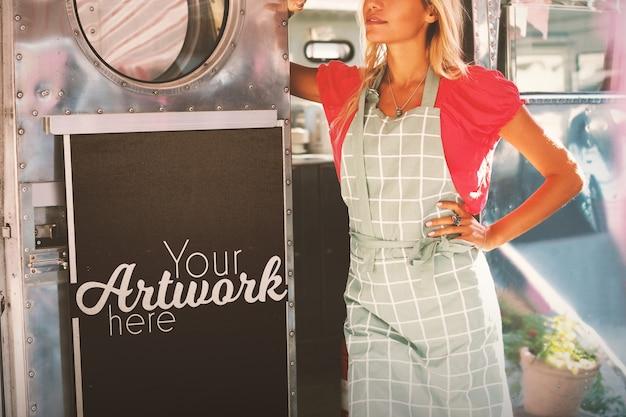 Camarera de pie en el camión de comida con una pizarra maqueta