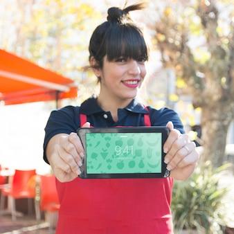 Camarera sujetando mockup de tablet para presentación de app