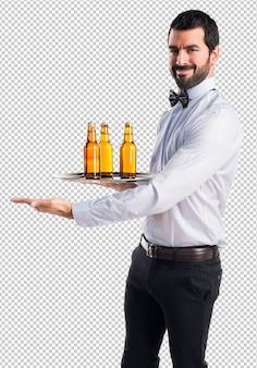 Cameriere con bottiglie di birra sul vassoio che presenta qualcosa