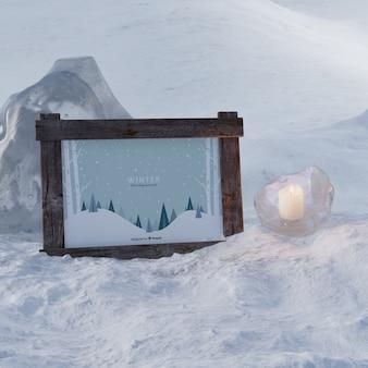 Candela congelata accanto al telaio con tema invernale