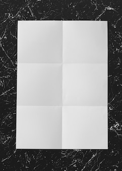 Carta bianca piegata su mockup di marmo