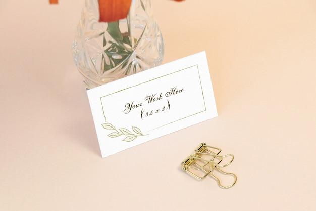 Carta di nome del mockup con vaso sul tavolo