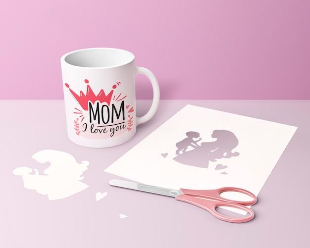 Carta e tazza di festa della mamma del primo piano con le forbici
