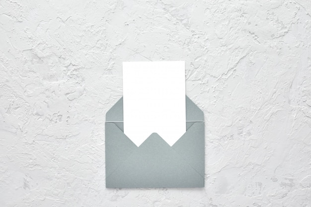 Carta in bianco bianca in busta su cemento