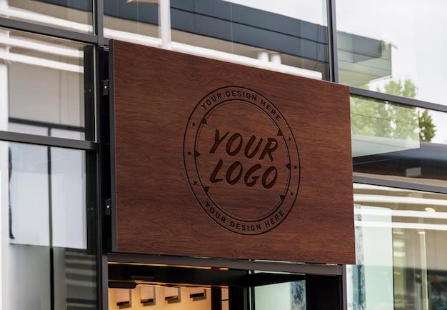 Cartel de madera grabado al aire libre en la ventana de la tienda maqueta