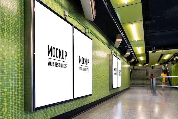 Cartelera en blanco ubicada en pasillo subterráneo o metro para publicidad, concepto de maqueta, obturador de baja velocidad de luz