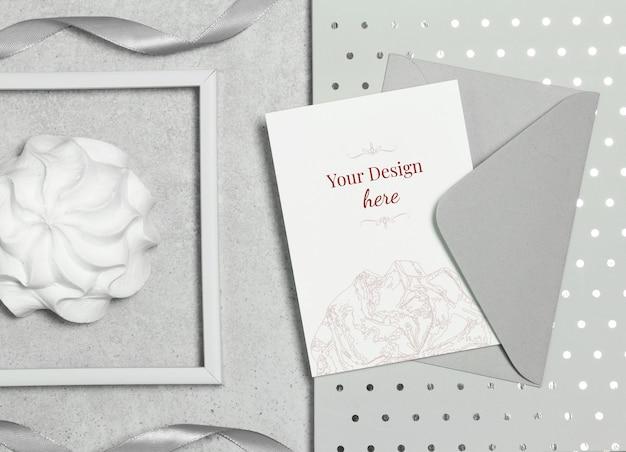 Cartolina di mockup su sfondo grigio con busta, marshmallow e cornice