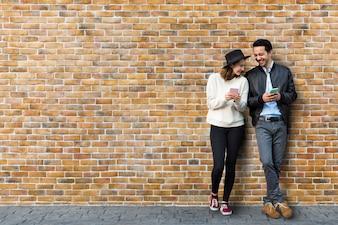 Casal namorando na frente da parede de tijolo