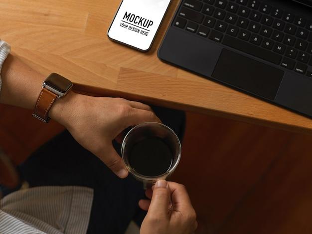 Cerca de manos masculinas sosteniendo la taza de café en el espacio de trabajo con maqueta de teléfono inteligente