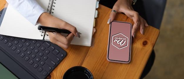 Cerca de las manos sosteniendo la maqueta de la pantalla del teléfono inteligente
