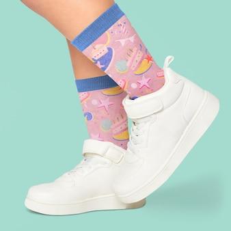 Cerca de los pies con calcetines y maqueta de zapatillas
