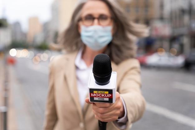 Cerca de reportero sosteniendo maqueta de micrófono