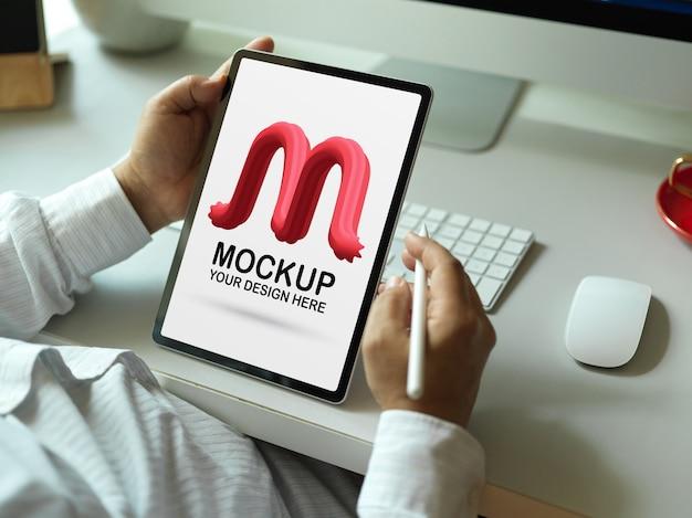 Cerca de trabajador de oficina masculino sosteniendo la maqueta de una tableta digital
