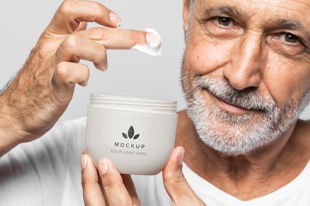 Cerrar hombre senior con recipiente de crema