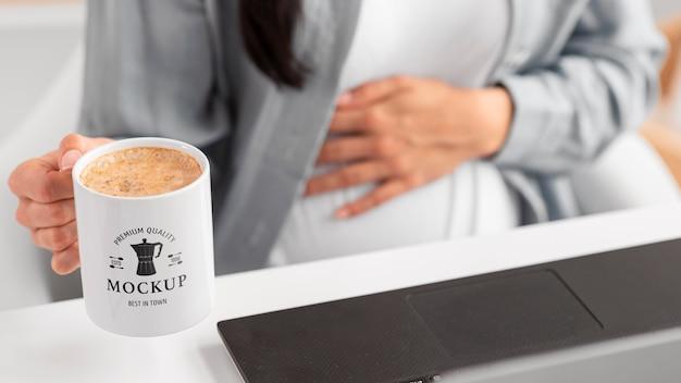 Cerrar la taza de explotación de mujer de negocios embarazada