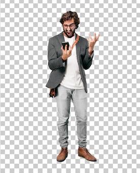 Chaqueta que lleva del hombre de negocios barbudo joven usando un teléfono elegante