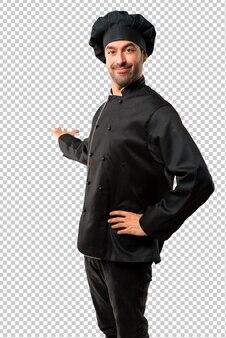 Chef hombre en uniforme negro apuntando hacia atrás con el dedo índice presentando un producto
