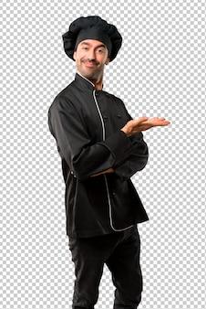 Chef hombre en uniforme negro que presenta un producto o una idea mientras mira sonriendo hacia