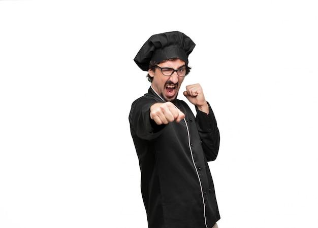 Chef joven con una pose enojada, agresiva y amenazante, listo para la pelea
