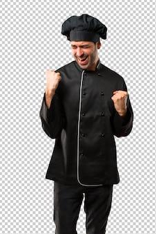 Chef-kok in zwart uniform een overwinning vieren en blij dat hij een prijs heeft gewonnen